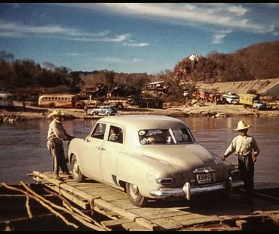 Car crossing Mexican river on poled raft